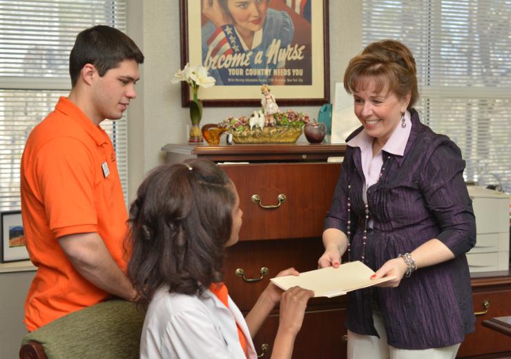 The nursing dean hands a folder to a student