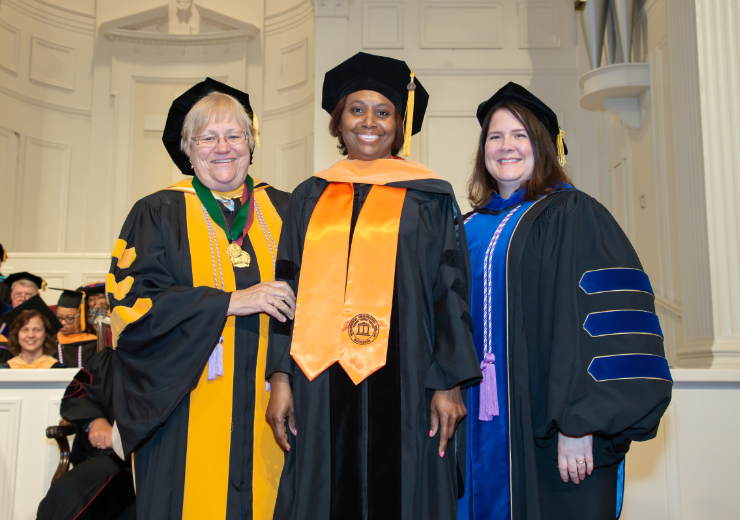 A DNP graduate is flanked by two faculty members during graduation
