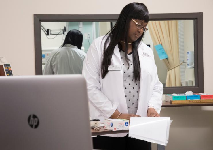 a nursing student wears a white lab coat