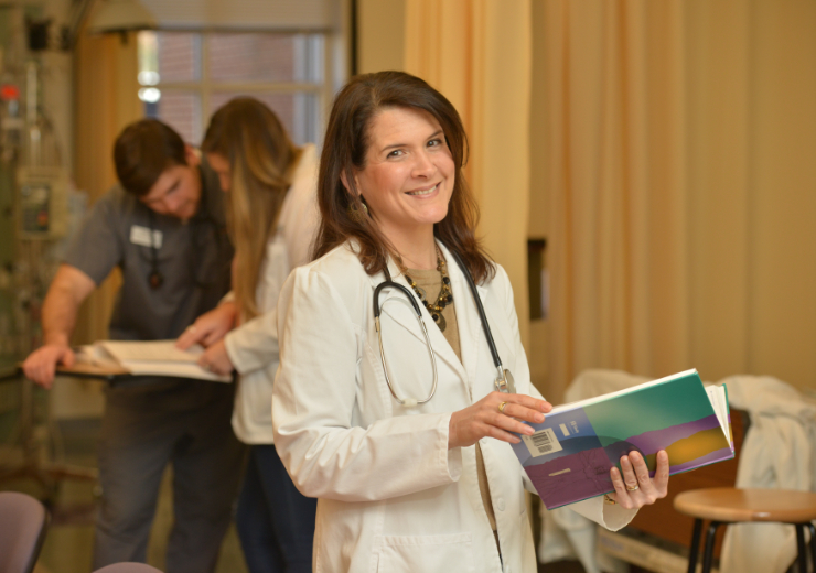 a woman in a white coat holds a textbook