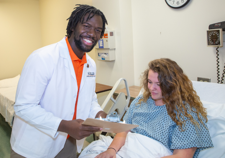 A nursing student pictured with a patient in a hospital bed