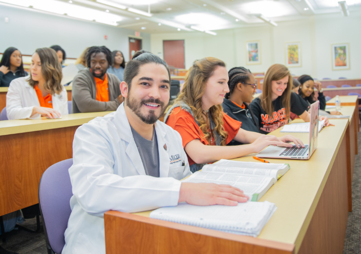 a nursing student sits in class surrounded by other students