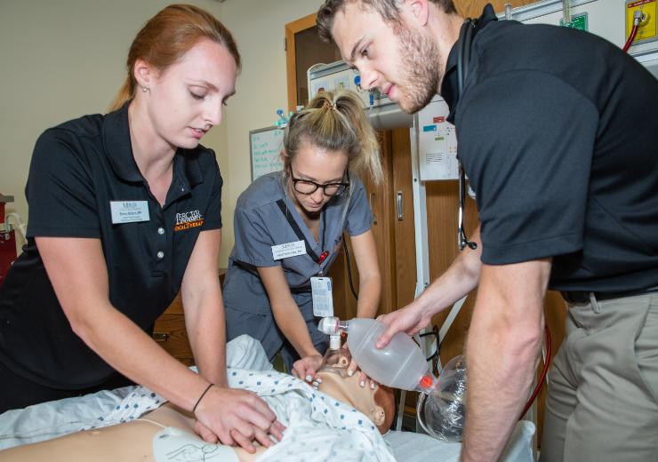 three nursing students perform CPR on a dummy