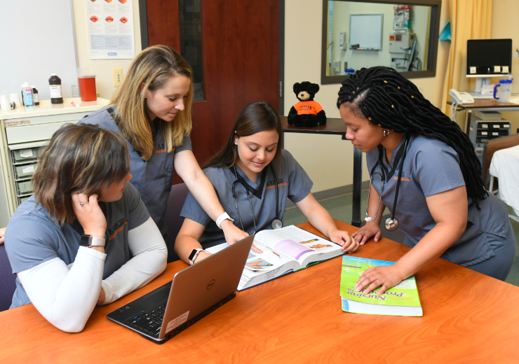 Four female nursing students gather around a computer and textbook