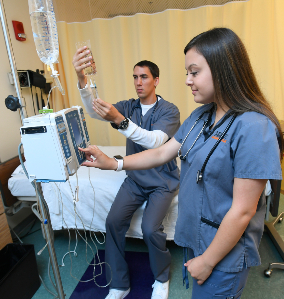 Two nursing students administer medicine through an IV